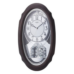 "Rhythm Clocks - 21"" x 12"" Crystal Hearts Musical Clock Silver - This clock elegantly displays a silver-finished face with an elongated espresso-finished frame. The pendulum features heart-shaped figures containing glimmering crystals. As the hour strikes, be captivated by the melodies played by the Crystal Hearts. Quartz clock is battery operated."