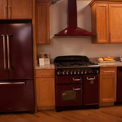 LumberTown Appliances - A complete set of red kitchen appliances shown with light hardwood floors and honey colored shaker cabinets.