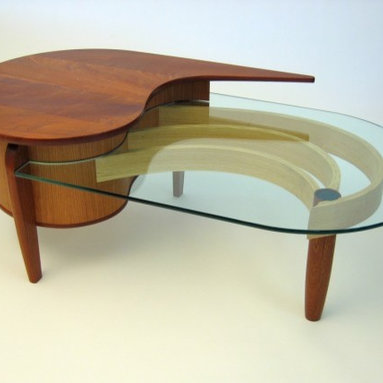Signature Table by Dogwood Design - This dual layer coffee table is made of vacuum formed plywood with quarter-sawn cherry veneer over. The top and legs are sapele, the drawers secondary wood are ash and jatoba. The curved pieces under the glass are bent lamination ash. Also, a small piece of fused glass on the top of the round leg adds a splash of color.