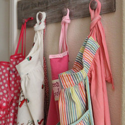 """Products - This hand painted wood apron hanger is the perfect pit stop for those cute aprons that have been stashed away in a drawer.  It has a cute saying on it, """"Never too many cooks in this kitchen!""""  If you'd like something else, please inquire.  It also has 4 knobs for hanging."""