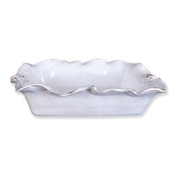 Fleur de Lis Rectangular Casserole - The Fleur de Lis Casserole's freeform ruffled edge gives a depth and interest to the deep rectangular dish, rippling below the applied French heraldic marks sculpted on either shorter side of the casserole. This lustrous glazed ceramic baking and serving piece drives away the mundane from your table setting with its exquisite originality, all in white glaze over a unique dark clay.