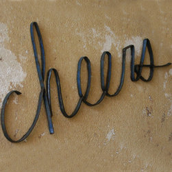 "Scrap Iron Cheers Wall Sign - Originally discarded rings of fifty-five gallon drum lids - now an object of desire. Spread good cheer with our scrap metal cheers sign. Dimensions: 32""w x 12""h"