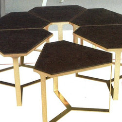 Donghia Showroom - Forma tables in high-luster satin brass with stone tops by Donghia