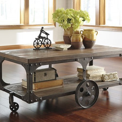 Rustic/Reclaimed - Ashley Furniture's Rustic Accents rectangular cocktail table is inspired by a factory cart complete with metal brackets and cast metal wheels. Relaxed and casual, this accent furniture collection has details that make a statement about the environment in we choose to live. (ashT500-721)