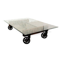 Kathy Kuo Home - Pittsburgh Industrial Reclaimed Cast Iron Coffee Table Cart - Life happens in the living room, so it's only fitting that your furniture in this space should be simultaneously stunning and functional. Such is certainly the case with this one of a kind coffee table, which a features recycled cast iron base and wheels topped with a tempered glass top. Let the light shine in with a piece that feels substantial but not heavy, thanks to the brilliant composition of reclaimed wood and cast iron contrasted with light as air glass. Let the gatherings begin!  Enjoy a one year warranty on this piece.