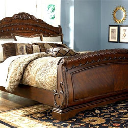 Millwood by ivgStores - Sleigh Bed w Slatted Headboard and Dark Brown - Choose Size: QueenCarved accents and graceful curves give this classic sleigh bed a stunning profile that will easily enhance your bedroom decor. The bed has an ornate charm that will make it a treasured addition to your space, and is made of wood in dark brown finish. It is available in your choice of sizes. Collection: North Sea. Sleigh Bed includes Headboard, Footboard, and Rails. Color/Finish: Dark Brown. Constructed with select hardwood veneers, hardwood solids and furniture grade resin. Dark casual finish. Dark colored metal accents & hardware. Large scale decorative pilasters and ornately detailed appliques. Mansion sized poster bed with upholstered headboard panel. Inlaid marble veneer caps on panel footboard. Queen Headboard: 65 in. W x 11 in. L x 62 in. H. Queen Footboard: 67 in. W x 11 in. L x 34 in. H. King/California King Headboard: 82 in. W x 11 in. L x 62 in. H. King/California King Footboard: 84 in. W x 11 in. L x 34 in. H