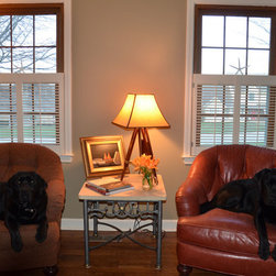 Traditional Shutters - Cafe height traditional shutters installed on windows in a reading room. These white colonial shutters are a stylish solution for privacy and light control. Plus they keep the dogs happy.