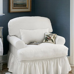 Chloe Ruffle Slipcover Chair - A feminine addition to a boudoir or sunroom, Chloe is a casual, relaxed haven for watching movies or curling up with a good novel. Styled with inviting proportions and generous padding, it features low rolled arms and decadently soft, down-wrapped cushions, including a lumbar pillow for added support. The upholstered muslin base and cushions are enveloped in a generous, antique ivory cotton slipcover finished with a gently gathered skirt.