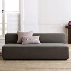 Baxter Sofa - Long, low and loungey. A relaxed seating option, this armless sofa's solid and substantial shape is lightened up by a beveled bottom edge and recessed, solid-wood base, which make it appear to float above the floor. An easy, simple canvas to personalize with decorative pillows and throws, it can be used on its own or as part of a sectional.