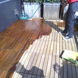 Custom Planters and Terrace Gardens by NYPLANTINGS - Restored IPE Deck, Sanded and oiled deck tiles,  NYC Terrace Garden Deck building, deck refinishing by New York Plantings Garden Designers oiling deck with lambs wool applicator