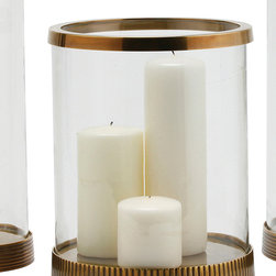 Bogart Brass/Glass Hurricane - Rich and warm, the metallic color of the Bogart Hurricane's polished vintage brass rim and lightly-corrugated antique brass base sets a tone of familiarity and opulence in your home.  Excellent for giving a varied patina to an arrangement of brass or gold accents, this generously-sized glass hurricane has a clear, simple chimney for flawless glamor on a tabletop or mantelpiece.