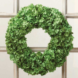 "Viva Terra - Green Hydrangea Wreath with Hanger - Introducing our ingenious and seasonally stunning alternative to poinsettias: a green hydrangea wreath on a grapevine base. Our floral designer grows his own hydrangeas by the ocean, then sun-bleaches the cut flowers and enhances them with food coloring. Glycerin keeps the petals pliable and adds a soft radiance to the wreath. Whether used as a centerpiece or hung on a wall or door, we suspect you'll want to save and store it for seasons to come. WREATH 15""DIAM, HANGER 13""L"