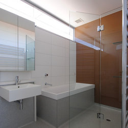 """Frameless Shower Enclosures - Another smaller bath located in NYC.  The shower area and tub area are combined.  The tub not having a deck made glazing this space with the frameless enclosure a bit challenging.  An operating splash panel was considered the best solution.  Sleek design and functional.  Glass is 3/8"""" standard clear.  Mirrored flush mount medicine cabinets."""