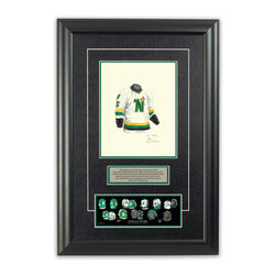 """Heritage Sports Art - Original art of the NHL 1985-86 Dallas Stars jersey - This beautifully framed piece features an original piece of watercolor artwork glass-framed in an attractive two inch wide black resin frame with a double mat. The outer dimensions of the framed piece are approximately 17"""" wide x 24.5"""" high, although the exact size will vary according to the size of the original piece of art. At the core of the framed piece is the actual piece of original artwork as painted by the artist on textured 100% rag, water-marked watercolor paper. In many cases the original artwork has handwritten notes in pencil from the artist. Simply put, this is beautiful, one-of-a-kind artwork. The outer mat is a rich textured black acid-free mat with a decorative inset white v-groove, while the inner mat is a complimentary colored acid-free mat reflecting one of the team's primary colors. The image of this framed piece shows the mat color that we use (Hunter Green). Beneath the artwork is a silver plate with black text describing the original artwork. The text for this piece will read: This original, one-of-a-kind watercolor painting of the 1985-86 Minnesota North Stars (now Dallas Stars) jersey is the original artwork that was used in the creation of this Dallas Stars uniform evolution print and tens of thousands of other Dallas Stars products that have been sold across North America. This original piece of art was painted by artist Nola McConnan for Maple Leaf Productions Ltd. Beneath the silver plate is a 3"""" x 9"""" reproduction of a well known, best-selling print that celebrates the history of the team. The print beautifully illustrates the chronological evolution of the team's uniform and shows you how the original art was used in the creation of this print. If you look closely, you will see that the print features the actual artwork being offered for sale. The piece is framed with an extremely high quality framing glass. We have used this glass style for many years with exc"""