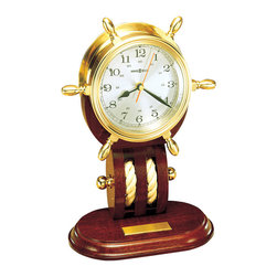 "Howard Miller - Howard Miller - Britannia Table Clock - Ahoy matey! This ship wheel mantle clock will make anyone feel like a sailor. Or maybe a pirate! Polished and lacquered solid brass ship's wheel clock rests on a mahogany base. Spun silver tone Arabic numeral dial make this the real treasure. * Polished and lacquered solid brass ship's wheel clock rests on a mahogany base which features nautical rope and brass knob detailing. . Spun silver tone Arabic numeral dial and 24-hour time track. . Beveled glass crystal. . Brass self-adhesive, engravable plate with polished beveled edges. . Quartz, battery operated movement. . H. 12-1/2"" (32 cm). W. 8-1/2"" (22 cm). D. 5"" (13 cm)"