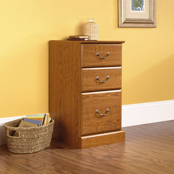 "Sauder - Orchard Hills Three Drawer Pedestal in Carolina Oak - American country style that provides endless versatility in the Orchard Hills Collection. Solid cases are softened by finely detailed moldings and brass-finished hardware, while warm Carolina Oak finish makes this piece the perfect accompaniment to the existing decor of any home. Features: -Pedestal. -Orchard Hills collection. -Carolina oak finish. -Two small drawers with metal runners and safety stops. -Lower drawer with full extension slides for letter size hanging files. -Patented T-lock drawer system. -Assembly required. -Manufacturer provides 5 year warranty.-Overall dimensions: 28.88"" H x 15.5"" W x 16"" D."
