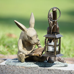 "Reading Rabbit Garden Lantern - The bespectacled bunny shares some light reading with a low profile garden lantern. Aluminum statuary/light fixture would make a great addition to the back porch or near a set of deck stairs. Dimensions: 11""w x 10""d x 10.5""h"