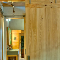 "Josh Wynne Construction - Custom 2 1/4"" solid cypress doors. Door cores are reclaimed from the scrap from the roof framing. Hardware is custom made exposed track, farm style in stainless steel."