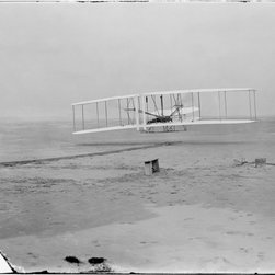 First Flight, 120 feet in 12 seconds Print - First flight, 120 feet in 12 seconds, 1903 Dec. 17 at 10:35 a.m.; Kitty Hawk, North Carolina. This negative shows Orville Wright at the controls of the machine, lying prone on the lower wing with hips in the cradle which operated the wing-warping mechanism. Wilbur Wright running alongside to balance the machine, has just released his hold on the forward upright of the right wing. The starting rail, the wing-rest, a coil box, and other items needed for flight preparation are visible behind the machine. Photograph attributed to Wilbur and/or Orville Wright. Photograph shows the first powered, controlled, sustained flight. Orville Wright preset the camera and had John T. Daniels squeeze the rubber bulb, tripping the shutter.