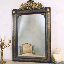 Black and Gold German 1930s Mirror - 1930 German style mirror made of wood with a black and gold leaf finished. The frame of the mirror has Griffin carvings atop the piece. The mirror is flat polish and is still fully reflexive.