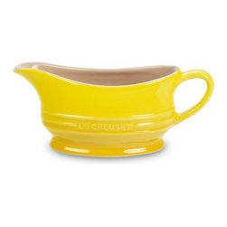 Le Creuset - Le Creuset 12 oz. Gravy Boat - Soleil - PG9700-121M - Shop for Bowls and Candy Dishes from Hayneedle.com! The bright yellow finish of the Le Creuset 12 oz. Gravy Boat Soleil will add a burst of sunny delight to your dining table. The high-quality stoneware construction is sturdy and durable sure to last many years of enjoyment. With a 12-ounce capacity this mini pitcher is perfect for serving gravy hollandaise and any other sauce needed at your gathering. For easy cleanup this gravy boat is dishwasher safe. About Le Creuset of America Inc.From its cast iron cookware to its teakettles and mugs Le Creuset is a global standard of inimitable color and quality. Founded in 1925 in the northern French town of Fresnoy-Le-Grand Le Creuset still produces enameled cast iron in its original foundry. Its signature color Flame was modeled after the intense orange hue of molten cast iron within a cauldron (or creuset in French) and has been a Le Creuset bestseller from the company's first year to the present day.Though best known for its vibrantly colored cookware and original inventions such as the Dutch oven Le Creuset has also forged a name as a creator of stoneware mugs and enamel-coated stainless steel teakettles. The style and performance of Le Creuset's Cafe Collection and tea accessories are rooted in classic French cookware: bold colors cylindrical loop handles unmatched thermal resistance and heat distribution and of course the iconic Le Creuset three-ring accent. Through its consistent qualities of authenticity originality and innovation Le Creuset maintains a connection to both heritage and modernity.