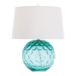 Caprice Aqua Glass Lamp - A blue glass globe accented with evenly sized circular impressions makes a sophisticated design statement with oceanic allure. Cool and playful, the short style hits an edgy high note with its oversized white drum shade.