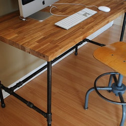 Industrial Desk with Oak Top and Steel Pipe Legs by Urban Wood Goods - With a butcher-block top and solid-steel-pipe legs, I doubt a more sturdy desk has come along since the steel tanker desk. This piece is full of character and comes at a very reasonable price for something handmade.