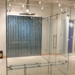 Walk-in shower with sliding barn door, glass bench and mirrored wall paper -