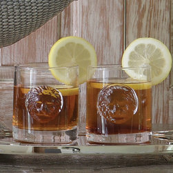 Double Old Fashioned Leo Drinking Glasses - Set of 4 - Lordly serving of simple spirits makes fireside conviviality and after-dinner lingering all the more elegant.  The Double Old Fashioned Leo Drinking Glasses are adorned with three-dimensional round lion's faces, adding a subtle touch of heraldic right to their classic, solid shape.  Thick, straight walls make drinking pleasant and mixing effortless with these grand glass tumblers.