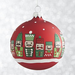 "Red Nutcracker Ball Ornament - Entire ""armies"" of stylized modern nutcracker soldiers are handpainted with detailed mustaches, hats and uniforms with glitter accents. They stand in snow on handmade glass ornaments with matte green, red or white finishes."
