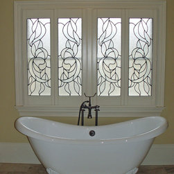 Elite Shutters in Bathroom Settings - This is a custom bi-fold shutter that Elite built for a bathroom window with a stained glass panel insert.