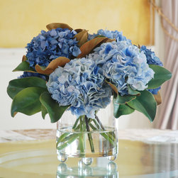 Blue Forest Hydrangea   Fourth Of July Promo - What could be more charming than lush, blue clusters of pompom blooms? In a bed of magnolia leaves, this exquisite arrangement feels classic contemporary. The small-footed detail of the vase makes this arrangement extra special. It's a look you'll love — forever! With our flowers reputably known for its life-like resemblance, you'll be pleasantly surprised at the way this arrangement will liven up your room.