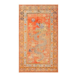 Consigned Antique Silk Dragon Khotan Rug from East Turkestan - Antique Silk Dragon Khotan Rug, East Turkestan, circa Turn of the Twentieth Century - Here is an intriguing and unique antique Oriental rug - an antique silk dragon rug that was woven in East Turkestan around the turn of the twentieth century. In addition to showing its age so beautifully, this captivating Khotan carpet boasts a remarkable dragon design. While originating in East Turkestan and being woven in the Khotan tradition, this antique carpet is in fact a beautiful example of the sort of traditional Chinese imagery that is often to be found in rugs that originate from China. A pair of borders run along the perimeter of the carpet: The outer border features stylized cloud hands, while the inner border features an intriguing floral and vine scroll detail. The field, however, is certainly the focal point of the carpet. Here, set against a fiery red background, stands an impressive five-clawed imperial dragon - the most desirable of all Chinese dragons. Characterized by a comely abrash, this antique Khotan dragon carpet is a unique and compelling example.