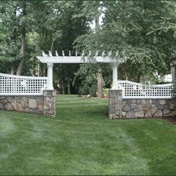 Vinyl Sloping Lattice Fence - Meticulously crafted sloping lattice sections follow the flow of the landscape and the handsome rock wall. The entrance is highlighted by a dramatic custom pergola structure.