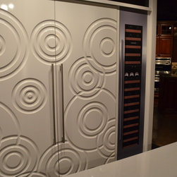 White Sub-Zero with Custom Panels - This custom Sub-Zero Refrigerator is fit with 70's style white panels with contemporary circles cut into the panels.