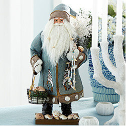 Seaside Santa - New - A coastal-inspired take on the man in red, this santa is decked in hues taken from the sea. He's constructed from wood, with a detailed, life-like face and real shells. Incorporate him into your holiday collection for a splash of maritime cheer. Sits on a tabletop.