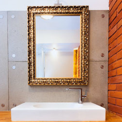 Bathroom mirror on gold frame - The frame's moulding is a series of embossed panels. The finish has a dark gold with light gray wash.
