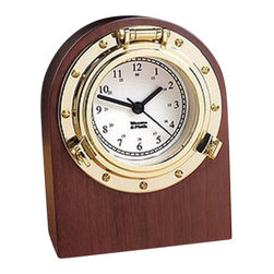"Weems & Plath Porthole Desk Clock - This nautical style porthole desk clock is inset in solid American hardwood that has a mahogany finish and a scratch resistant sole. The polished brass finish of the quartz clock will never tarnish. It is perfect for the home or office and has a lifetime warranty. An engraveable brass plate for personalization is included. It measures 6.5"" H x 4.4""W x 2.75""D."