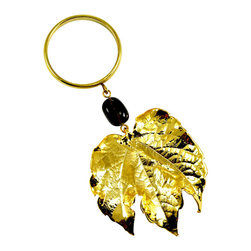 Grape Leaf Wine Charm in 24-karat Gold - If you like sparkling wine, here's a way to get it with baubles instead of bubbles. A natural grape leaf, preserved in either 24-karat gold or iridescent, hangs from a glass bead and brass ring large enough to fit over your wine bottle. Or, use it to add sparkle to your table as a napkin ring.