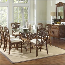 "Hospitality Rattan Cancun Palm Indoor 7 Piece Rattan & Wicker Rectangular Dining - Enjoy the tropical breeze in good company when you and those close to you relax around the Hospitality Rattan Cancun Palm Indoor 7 Piece Rattan & Wicker Rectangular Dining Set - TC Antique - Seats 6. This durable, indoor set will easily support six folks with chairs and a table crafted from sturdy rattan poles with leather bindings. Each seat offers up a plush, neutral-shaded cushion and a casting of the repeating fiber palm-motif that makes this set stand out. The table base also shares the palm design as well as the deep antique finish. The extra-long glass top is formed from a single sheet of tempered and beveled glass that's durable enough for daily use and easy to clean. Dimensions:Chair: 20W x 23D x 38H inchesTable: 62L x 42W x 30H inchesAbout Hospitality Rattan Hospitality Rattan has been a leading manufacturer and distributor of contract quality rattan, wicker, and bamboo furnishings since 2000. The company's product lines have become dominant in the Casual Rattan, Wicker, and Outdoor Markets because of their quality construction, variety, and attractive design. Designed for buyers who appreciate upscale furniture with a tropical feel, Hospitality Rattan offers a range of indoor and outdoor collections featuring all-aluminum frames woven with Viro or Rehau synthetic wicker fiber that will not fade or crack when subjected to the elements. Hospitality Rattan furniture is manufactured to hospitality specifications and quality standards, which exceed the standards for residential use. Hospitality Rattan's Environmental Commitment Hospitality Rattan is continually looking for ways to limit their impact on the environment and is always trying to use the most environmentally friendly manufacturing techniques and materials possible. The company manufactures the highest quality furniture following sound and responsible environmental policies, with minimal impact on natural resources. Hospitality Rattan is also committed to achieving environmental best practices throughout its activity whenever this is practical and takes responsibility for the development and implementation of environmental best practices throughout all operations. Hospitality Rattan maintains a policy of continuous environmental improvement and therefore is a continuing work in progress. Hospitality Rattan's Environmentally Friendly Manufacturing Process All of Hospitality Rattan products are green. From its basic raw materials of rattan poles, peels, leather, bamboo, abaca, lampacanay, wood, leather strips, and boards, down to other materials like nails, staples, water-based adhesives, finishes, stains, glazes and packing materials, all have minimum impact to the environment and are safe, biodegradable, recycled, and mostly recyclable. Aside from this, the products have undergone an environmentally-friendly process that makes them """"greener."""" The company's rattan components are sourced from sustained-yield managed forests, which means the methods used to grow and harvest the rattan vines ensure the long-term life of the forest and protect the biodiversity of the forest's ecosystems. Hospitality Rattan is committed to buying and using all materials, from rattan and hardwood to finishing materials, from reputable and renewable suppliers and seeks appropriate evidence that suppliers are in compliance with this policy. Hospitality Rattan strives to use materials that are processed in an environmentally responsible manner, or consist of a high level of recycled material. Finishing materials and stains used in Hospitality Rattan's furniture products consist of 75% water-based solutions which evaporate upon application with reduced or Volatile Organic Compounds (VOCs). The furniture factories use water-based glues, stains, topcoats and other finishes on all of their products. The switch from traditional solvent-based processes to water-based processes involved consolidating several processes by the factories, resulting in an 85% reduction in VOC emissions."