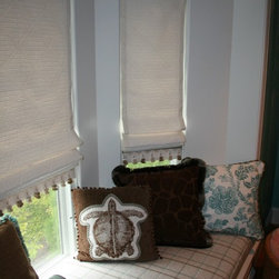 Roman Shade Variations:  Closeup of Flat Roman at Window Seat - In this closeup photo of the window seat, you can see the basket weave woven pattern of the fabric, and the multi-colored trim at the hem of the flat Roman shades.  The print fabrics are from Kravet's Captiva Island collection.