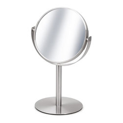 Blomus - Primo Stainless Steel Cosmetic Mirror - Freestanding. 2x Magnifying mirror on one side. Made of stainless steel, matte finish. Designed by Stotz-Design. 1-Year manufacturer's defect warranty. 7.5 in. Dia. x 13.23 in. H