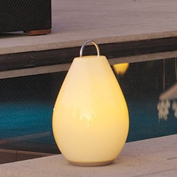 OXO - Luau Portable LED Lamp - The Luau Portable Lamp (2006) makes standard table lamps look so, well, stationary. Suitable for indoor and outdoor use, Luau is a lighting solution that delivers dimmable light without being tethered to an electrical socket. Luau can be used while recharging. When lifted from its base, the lamp automatically lights and glows for 6-10 hours. Adjust the amount of warm ambient light by spinning the dial on the bottom of the lamp. Luau can sit on a surface or hang from a hook or tree branch by its stainless steel handle. Made of impact-resistant polyethylene with a water resistant housing. Energy-efficient LED pack and rechargeable 1500mAh battery included. Not intended for children under six. UL Listed