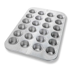 USA Pans 24 Cup Mini Muffin Pan - The USA Pan 24 cup mini muffin pan has been designed with many of the same standard features of industrial baking pans.  Each pan is constructed of aluminized steel  the material of choice for commercial bakeries.  Metal thicknesses have been selected that allow even heat distribution and maximum service life.  Our pans also use steel wires in the rim construction of most pans to provide additional strength and resist warping.  Each pan is coated with AMERICOAT Plus  a proprietary silicone coating that nearly all North American bakers prefer over dark non-stick coatings.   AMERICOAT Plus is a clear non-stick  environmentally friendly coating that is specifically formulated for superior baking and does not contain any PTFE's or PFOA's.  USA Pan bakeware features a corrugated  or fluted  design.  The corrugation maximizes pan strength and prevents warping  denting and other effects of everyday use.  Corrugation also minimizes surface contact with baked goods which translates into an evenly baked product that is easily released. USA Pan has been developed by the world's largest manufacturer of industrial bakeware and has been providing the world's leading commercial bakeries with the highest quality baking pans for over 50 years.  When you purchase a USA Pan you are buying products that meet industrial standards for innovation  quality and durability.  Put simply  our pans are the best available and are proudly produced in the UNITED STATES OF AMERICA. Product Features                                   Constructed of heavy gauge aluminized steel             Corrugated design allows for even baking            Proprietary AMERICOAT  coating allows easy release of food            Proudly made in the USA for over 50 years