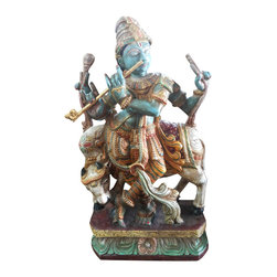 Wooden Krishna - Multi Color Finish - 3 Ft - This is the venugopala avatar of Krishna and Vishnu in the same form.  Krishna was a cow herder in hi syoung age. So a cows love for the lord has been depicted by she licking Krishna's feet.  The Lord is seen playing his favorite musical instrument- flute. This statue is carved by an artisan from southern part of India