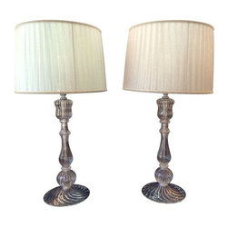 Pre-owned Italamp Blown Glass Table Lamp - A Pair - The Etvoila table lamp, manufactured by Italamp, is a beautiful example of Italian glass work. Evoking the lines and look of blown Mirano glass, this table lamp brings a touch of modern European elegance to your room.     Made of clear glass and chrome hardware, this lamp has an extremely clean look. The base of these lamps are in perfect condition - no chips, scratches or damage of any kind. The lamp holds a single standard bulb. Both shades are  in good condition with one shade showing some sun fading.    These lamps have only appreciated in value over time owing to their high quality and design.     (Note: second photo is from Italamp product catalog for comparison purposes - photo of two lamps are the actual lamps.)