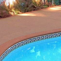 Re-surfaced Pool Deck by Rubaroc Safety Surfacing - Rubaroc Rubber Safety Surfacing is the innovative way to rejuvenate old, cracked, damaged or unsightly concrete, tile, interlock, slab, flagstone, brick, wood, metal or asphalt. Rubaroc is a 30-year proven product comprised of the highest quality, purpose-made rubber granules combined with specially formulated resin binder. Commonly referred to as 'poured-in-place', Rubaroc is hand troweled over imperfections and minor undulations creating a seamless, carpet-like surface that will last for years.