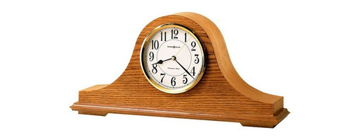 "Howard Miller - Nicholas Quartz Mantel Clock - Realign your room with this sense of tradition and quality. Reshaped with natural wood this selection slopes into a sturdy base, to manage an easy read atop of any mantle, bedside table and night stand. Great selection for any room. * The off-white dial offers a convex glass crystal, polished brass finished bezel, black Arabic numerals and brass second hand. . Quartz, battery operated movement will play Westminster chimes on the hour and also count the hour. . Finished in Golden Oak on select hardwoods and veneers. . Automatic nighttime chime shut-off option. . Quartz, battery operated movement.. H. 8-1/2"" (22 cm). W. 17-3/4"" (45 cm). D. 4-3/4"" (12 cm)"