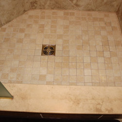 "Master Bathroom Remodel, Strongsville, OH #1 - We updated this master bathroom shower by installing Capri Tile Collection, Sandy Ridge Mosiacs Border 13 x 13 on the walls and 2 x 2 on the floors with 3 x 12 bullnose.  The Chrome Shower door is a 3/8"" Satin Glass Door (28"") with Stationary Panel, C-Pull combo handle, frameless, armor coated.  A Jaclo Polished Brass Jaylen Collection – Hand Shower and Bar was installed.  These showering systems have the ability for the shower head to work at the same time as the hand shower or they can operate independently.   A bench and cubby niche was installed."