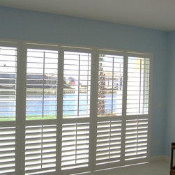 Window Treatments for Sliding Doors - Plantation shutters to mimic French doors.  Rather than use a traditional bypass on track plantation shutter or a bifold on track these shutters are mounted with T posts and open into the room